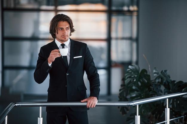 Portret van knappe jonge zakenman in zwart pak en stropdas staat binnenshuis met een kopje drank.