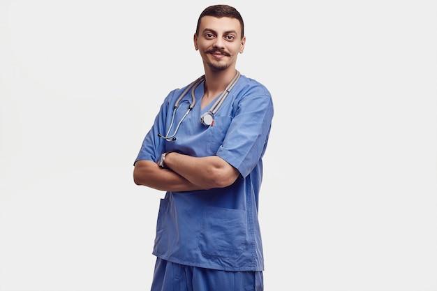 Portret van knappe jonge zekere arabische arts met buitensporige die snor in blauw op wit wordt geïsoleerd
