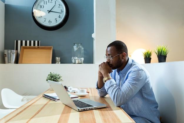 Portret van knappe jonge zwarte man aan het werk met laptop thuis.