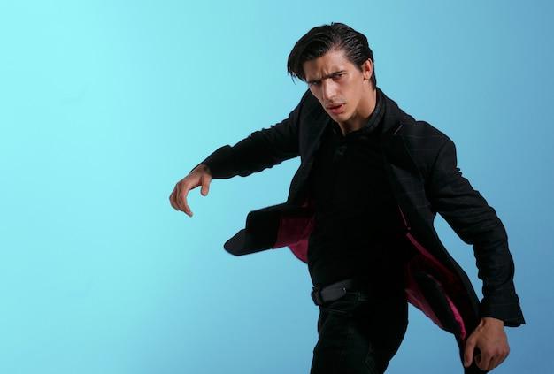 Portret van knappe jongeman in stijlvol zwart pak, roterende geïsoleerd op blauwe achtergrond. horizontale weergave.