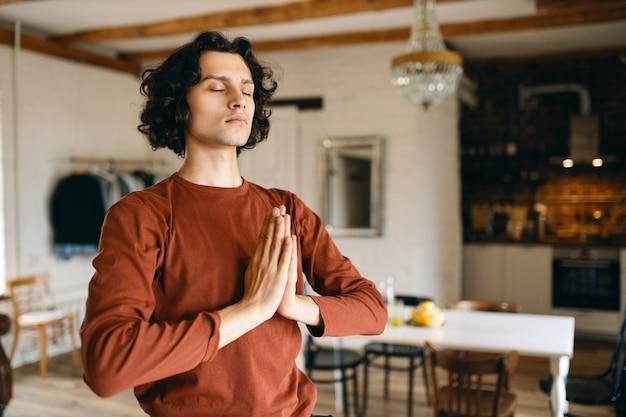Portret van knappe jongeman met zwart krullend haar poseren in gezellige keuken interieur ogen gesloten houden en handen samen in namaste drukken, bidden, meditatie doen, met rustige blik