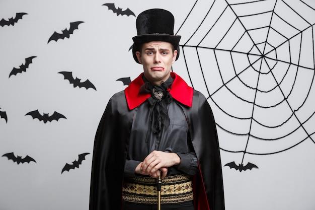 Portret van knappe kaukasisch in halloween-kostuum van de vampier met droevige gelaatsuitdrukking.