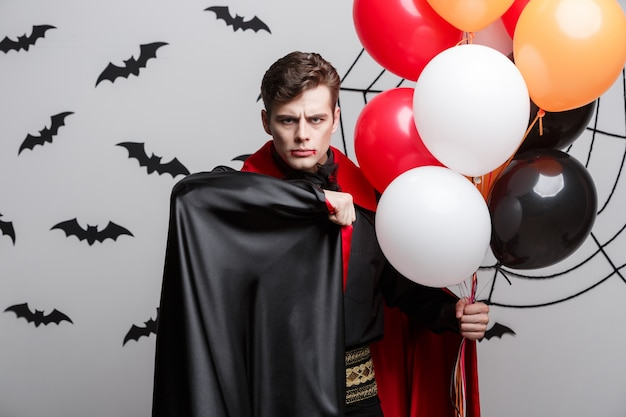 Portret van knappe kaukasisch in halloween-kostuum van de vampier met kleurrijke ballon.