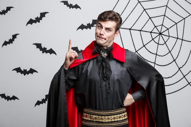 Portret van knappe kaukasisch in het kostuum van halloween van de vampier poining aan kant.