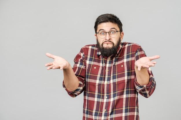 Portret van knappe kerel die bovenkant kijkt en zijn schouders ophaalt