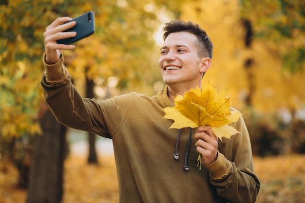 Portret van knappe kerel die een boeket van de herfstbladeren houdt en een selfie neemt