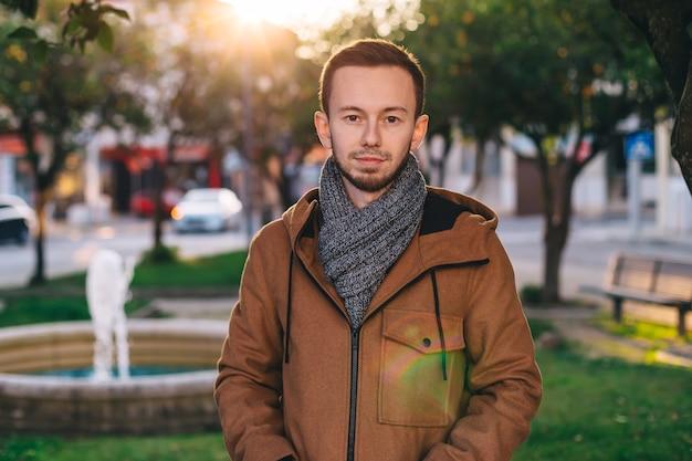 Portret van knappe kerel in jasje en sjaal. stad. kijk naar de camera.