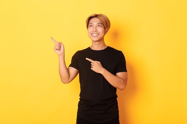 Portret van knappe koreaanse blonde kerel, wijzende vingers linkerbovenhoek en kijkt tevreden met tevreden glimlach, gele muur.
