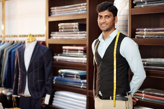Portret van knappe lachende indiase kleermaker met meetlint om zijn nek staande in atelier