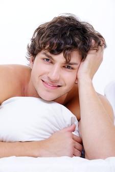 Portret van knappe lachende jonge man in de camera kijken