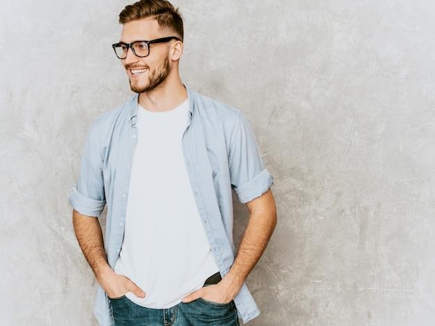 Portret van knappe lachende jonge man model casual shirt kleding dragen. mode stijlvolle man poseren in bril