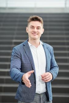 Portret van knappe lachende jonge ondernemer uitgestrekte armen voor handdruk en camera te kijken