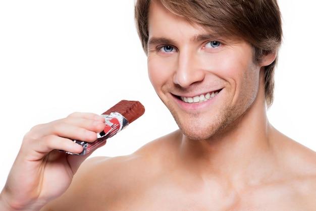 Portret van knappe lachende man met chocoladereep - geïsoleerd op wit.