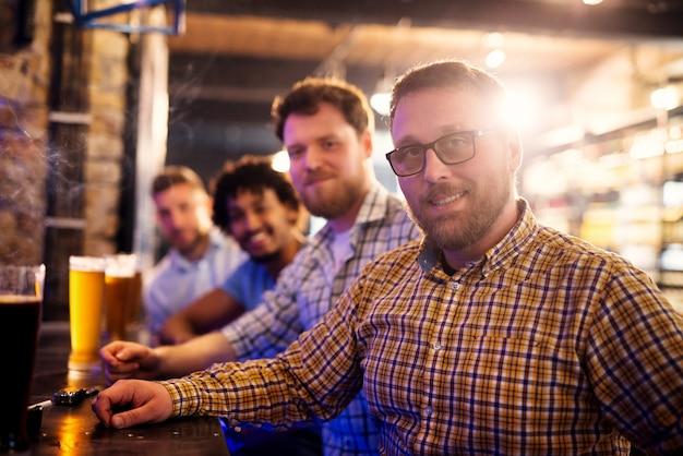 Portret van knappe lachende man zit in de bar met vrienden. glazen bier van de tap en rook van de sigaret vooraan.
