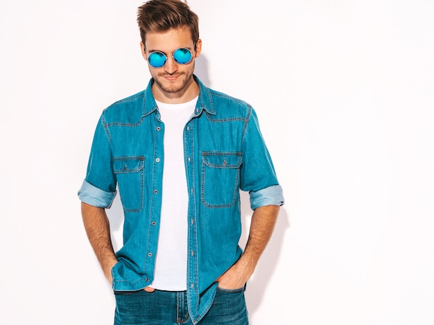 Portret van knappe lachende stijlvolle jonge man model dragen jeans kleding en zonnebril. mode man
