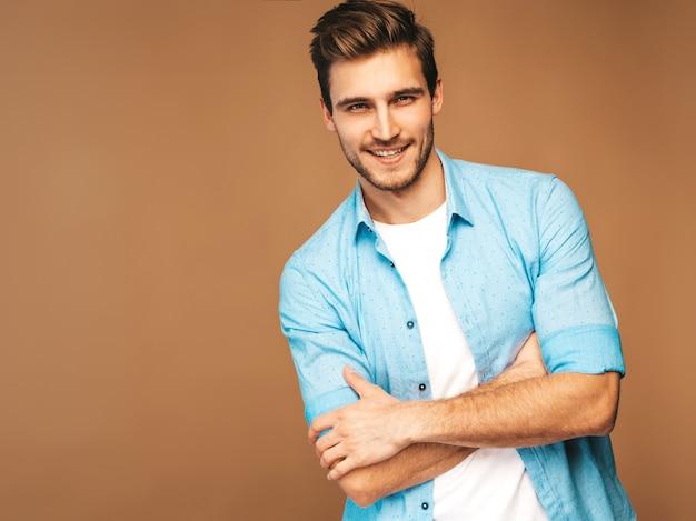 Portret van knappe lachende stijlvolle jonge man model gekleed in blauwe shirt kleding. mode man die zich voordeed. gekruiste armen