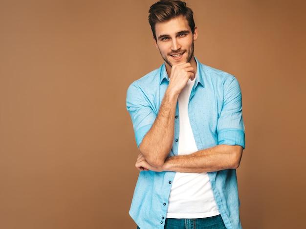 Portret van knappe lachende stijlvolle jonge man model gekleed in blauwe shirt kleding. mode man die zich voordeed