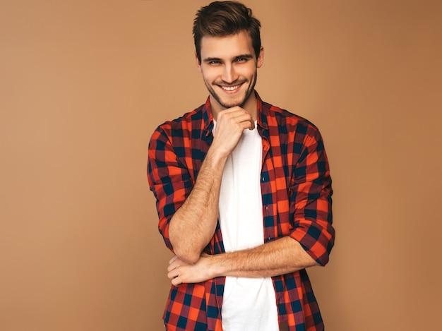 Portret van knappe lachende stijlvolle jonge man model gekleed in rood geruit hemd. mode man die zich voordeed. wat betreft zijn kin