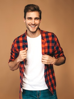 Portret van knappe lachende stijlvolle jonge man model gekleed in rood geruit hemd. mode man die zich voordeed