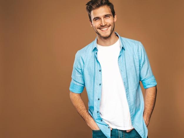 Portret van knappe lachende stijlvolle jongeman model gekleed in jeans kleding. mode man. het stellen