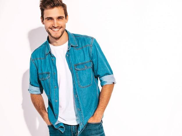 Portret van knappe lachende stijlvolle jongeman model gekleed in jeans kleding. mode man