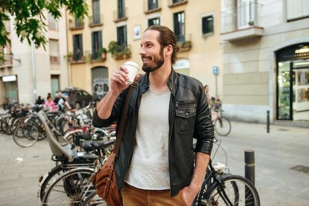 Portret van knappe man 30s dragen lederen jas afhaalmaaltijden koffie drinken tijdens wandeling op straat in de buurt van veel fietsen Premium Foto
