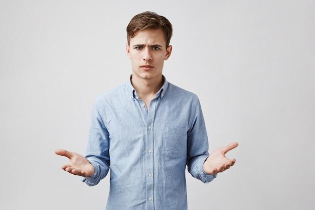 Portret van knappe man die onzeker kijkt. op zoek boos en ondervraagd