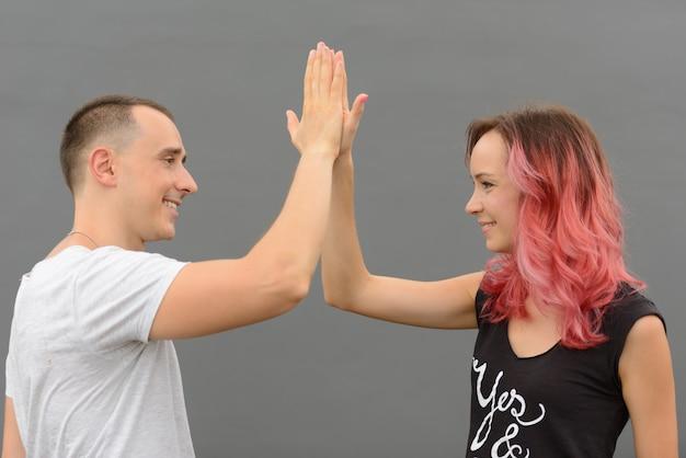 Portret van knappe man en mooie vrouw met roze haar als paar samen en verliefd tegen grijze muur buitenshuis