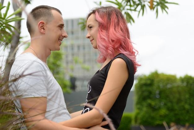 Portret van knappe man en mooie vrouw met roze haren als paar samen en verliefd in het park buiten