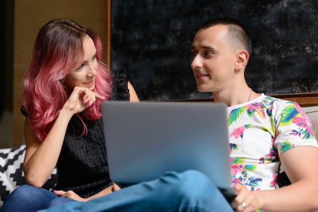 Portret van knappe man en mooie vrouw met roze haren als paar samen in de huiskamer