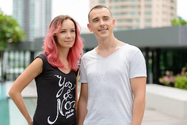 Portret van knappe man en mooie vrouw met roze haren als paar samen in het zwembad buiten
