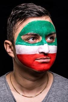 Portret van knappe man gezicht supporter fan van iran nationale team met geschilderde vlag gezicht geïsoleerd op zwarte achtergrond. fans van emoties. Gratis Foto