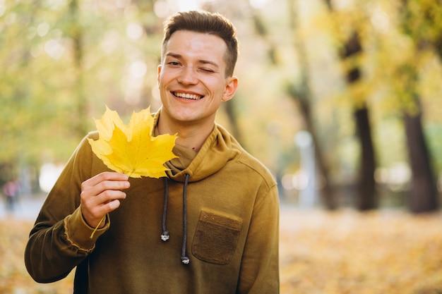 Portret van knappe man glimlachend en met een boeket van herfstbladeren in het park