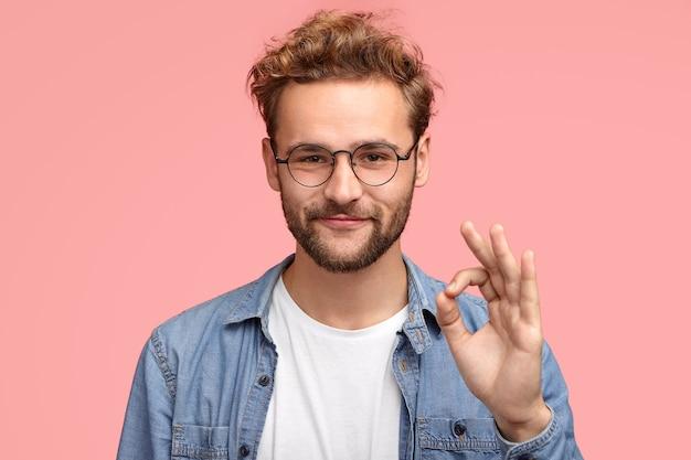 Portret van knappe man heeft stoppels, maakt ok teken, gaat akkoord of vindt iets leuk dat een vrolijke uitdrukking heeft, poseert tegen roze muur, bewijst dat alles volgens plan verloopt. lichaamstaal concept