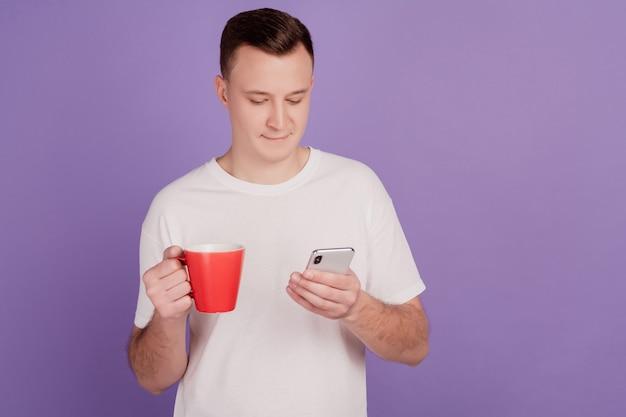 Portret van knappe man houdt mobiele telefoon drinken koffiemok op paarse achtergrond