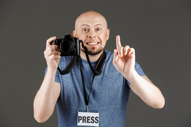 Portret van knappe man in grijs shirt met fotocamera en pers badge nemen van foto's over donkere muur