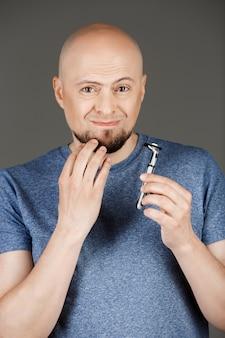 Portret van knappe man in grijs shirt met scheermes over donkere muur