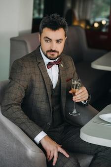 Portret van knappe man in pak houdt glas. een glas champagne in de hand van een brutale man