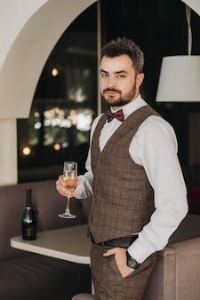 Portret van knappe man in pak houdt glas. een glas champagne in de hand van een brutale zakenman