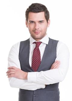 Portret van knappe man in pak met gekruiste armen muur.