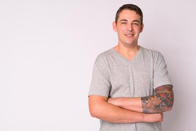 Portret van knappe man met armen tatoeages tegen witte muur