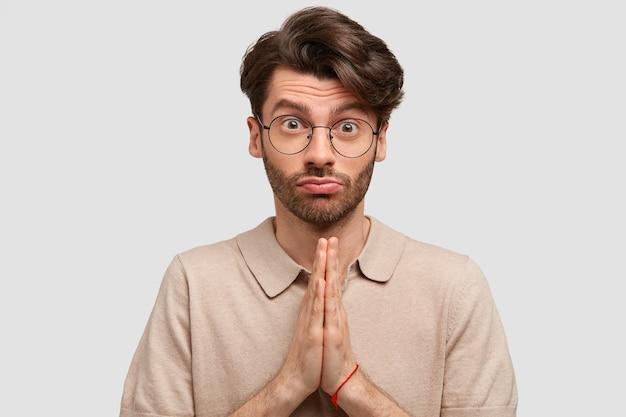 Portret van knappe man met europese uitstraling, houdt handen in gebed gebaar, vraagt om vergeving met ellendige uitdrukking, portemonnees lippen, terloops gekleed