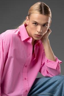 Portret van knappe man met lang blond haar en roze shirt pink