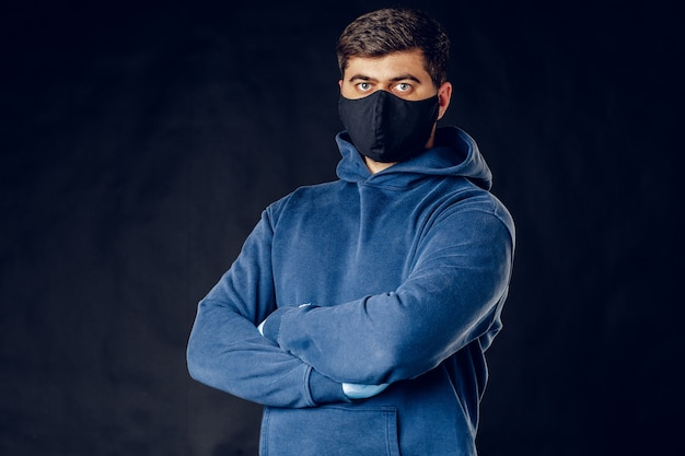 Portret van knappe man met medisch zwart masker op het gezicht tijdens virusepidemie lockdown poseren op donkere muur. detailopname.