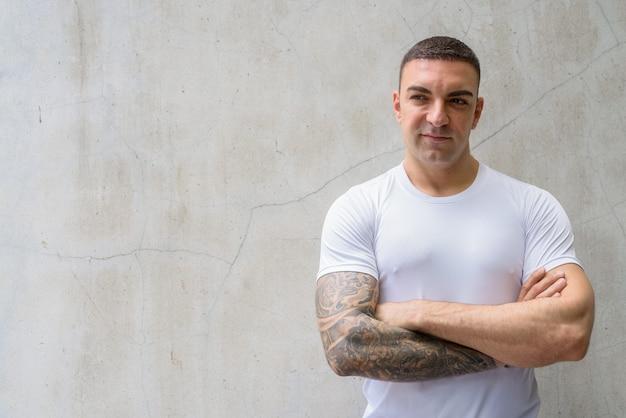 Portret van knappe man met tatoeages denken met gekruiste armen