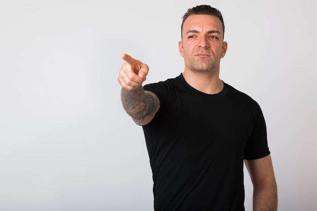 Portret van knappe man met tatoeages wijzende vinger