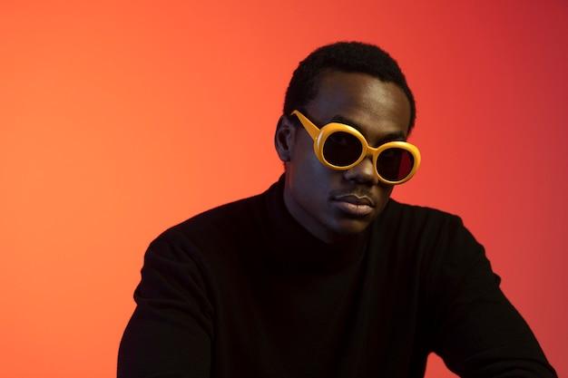 Portret van knappe man met zonnebril op oranje achtergrond