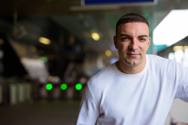 Portret van knappe man op het treinstation van de hemel in de stad
