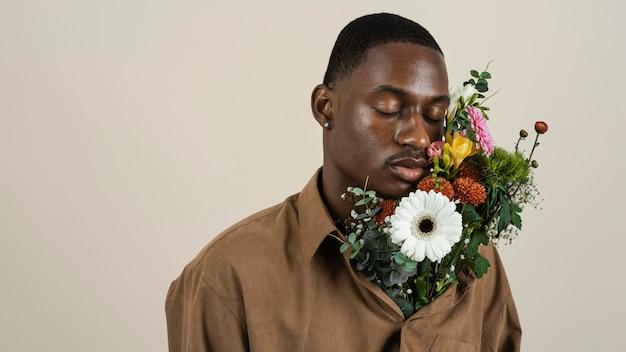 Portret van knappe man poseren met boeket bloemen