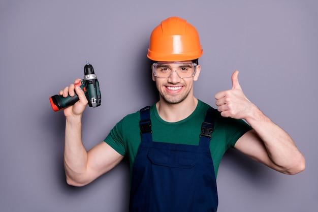 Portret van knappe man reparateur succesvolle klusjesman houden perforator duim omhoog teken dragen oranje harde hoed groen t-shirt beschermende bril geïsoleerd over grijze kleur muur